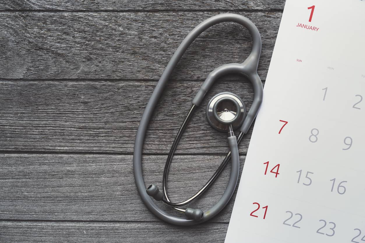 Top view of stethoscope and calendar on the table background, schedule to check up healthy concept